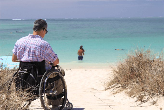 man in wheelchair at a beach